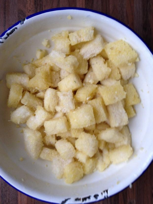 Snijd de korstjes van het brood. Snijd het brood in blokjes. Snijd de knoflook heel fijn (of pers het uit).